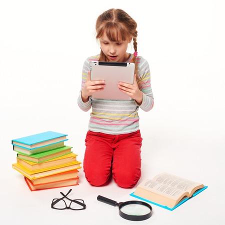 Prodigy: Nowa generacja. Mała dziewczynka siedzi na podłodze z dużą ilością książek, zakrywania twarzy z czytania książek, na białym tle Zdjęcie Seryjne