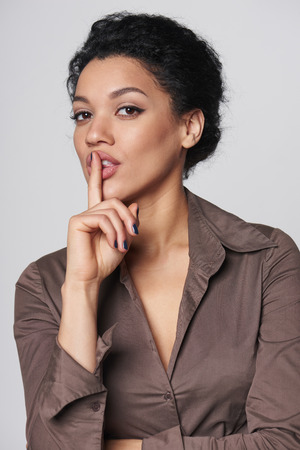 hushed: Hush. Portrait of mixed race caucasian - african american business woman with finger on her lips