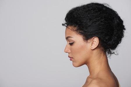 Beauty closeup profile portrait of beautiful mixed race caucasian - african american woman looking forward isolated on gray background Standard-Bild