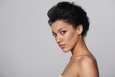 donna nuda: Bellezza del primo piano profilo ritratto della bella razza caucasica mista - donna african american guardando la fotocamera, isolato su sfondo grigio