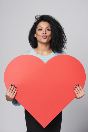 Happy african american girl holding big red heart shape and blowing you a kiss photo