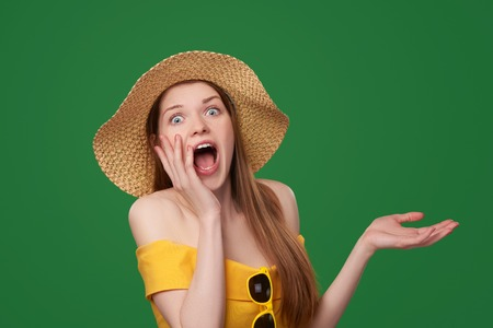 straws: Shocked surprised woman wearing bright yellow dress and summer straw hat showing open hand palm with copy space, over green background