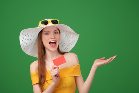 Excited surprised summer woman in yellow summer dress and a straw hat, showing blank credit card  and open hand palm with copy space for product or text, on green background photo