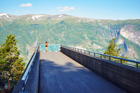 lookout: Woman enjoying scenics from Stegastein Viewpoint in a summer sunny day, Flam, Norway