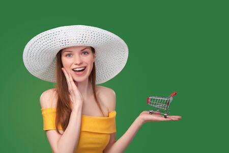 mujer alegre: Verano concepto de la venta de compras. Mujer brillante en vestido amarillo y un sombrero blanco que muestra el pequeño carro de compras vacío