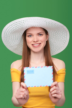 missive: Smiling bright woman in summer dress and white hat giving stretching blank envelope banner, shallow depth of field, focus at female