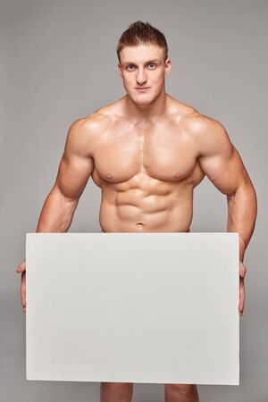 young guy: Muscular bare-chested maleholding white banner placard with copy space