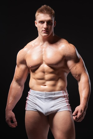men standing: Portrait of a young muscular man in underwear standing posing over black background Stock Photo
