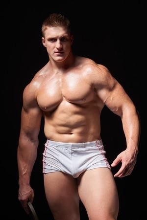 ropa interior: Retrato de un hombre musculoso joven de pie en ropa interior posando sobre fondo negro