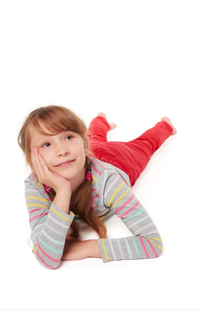 seven years: Front view of smiling child girl lying on stomach on the floor with head in hands looking away at blank copy space, over white background