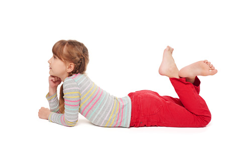 looking forward: Side view of smiling child girl lying on stomach on the floor with crossed legs looking forward, over white background Stock Photo