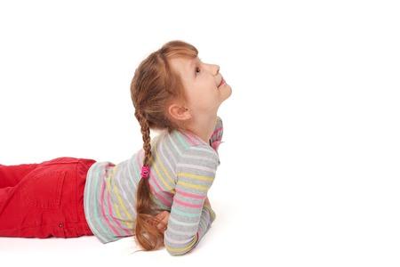 pantalones abajo: Vista lateral de la muchacha sonriente niño está acostado boca abajo en el suelo mirando al espacio de la copia en blanco, sobre fondo blanco