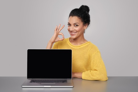 woman laptop happy: Happy mixed race african american - caucasian woman showing blank black laptop computer screen, looking at camera smiling, gesturing OK sign
