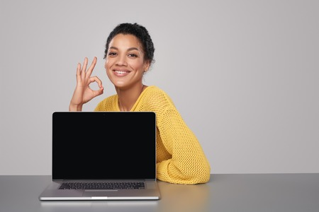 ok sign: Happy mixed race african american - caucasian woman showing blank black laptop computer screen, looking at camera smiling, gesturing OK sign