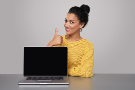computer table: Happy mixed race african american - caucasian woman showing blank black laptop computer screen, looking at camera smiling, gesturing thumb up