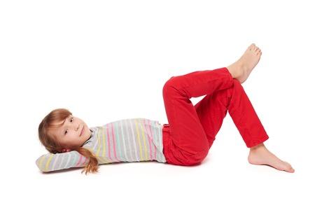 pantalones abajo: Vista lateral de la muchacha sonriente niña acostada de espaldas en el suelo con las piernas cruzadas mirando a la cámara, sobre fondo blanco Foto de archivo