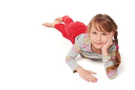 pantalones abajo: Vista frontal de la muchacha sonriente niño está acostado boca abajo en el suelo que mira la sonrisa de la cámara, sobre fondo blanco