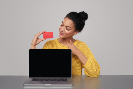 tumb: Smiling mixed race african american - caucasian woman showing blank black laptop computer screen and blank credit card, sitting at table, gesturing tumb up, over gray background Stock Photo
