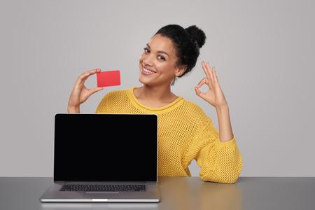 tarjeta de credito: Sonriendo raza mixta afroamericana - mujer caucásica que muestra la pantalla en blanco ordenador portátil negro y tarjeta de crédito en blanco, sentado en la mesa y que muestra signo de OK, sobre fondo gris Foto de archivo