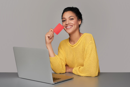 Happy laughing mixed race african american - caucasian woman with laptop computer showing blank credit card, sitting at table, over gray background