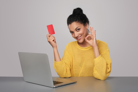 finance girl: Smiling mixed race african american - caucasian woman with laptop computer showing blank credit card, sitting at table  and gesturing OK sign, over gray background