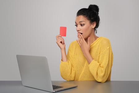 excited woman: Surprised mixed race african american - caucasian woman with laptop computer holding blank credit card, sitting at table, over gray background