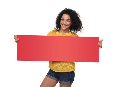 red banner: Happy casual mixed race african american - caucasian woman holding blank red banner, over white background