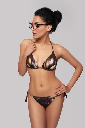 glasses model: Fashionable mixed race african american - caucasian woman in brown swimsuit and leopard print glasses posing