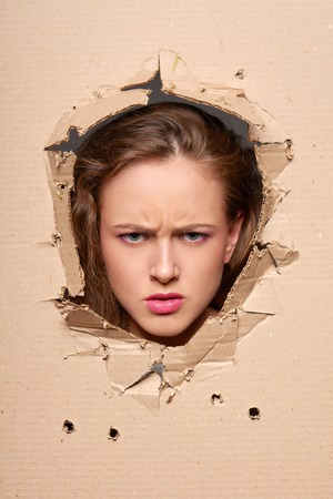 frantic: Displeased girl peeping through hole in paper