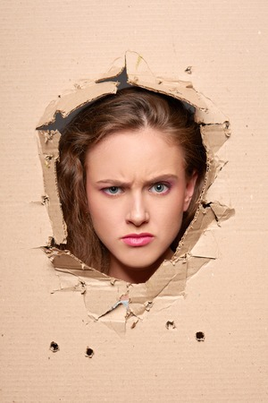 peeping: Confused girl peeping through hole in paper Stock Photo