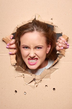 frantic: Emotional angry girl peeping through hole in paper Stock Photo