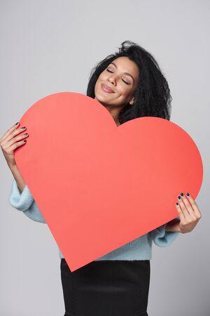 ojos cerrados: So�adora sonriente afroamericana chica sosteniendo forma gran coraz�n rojo con los ojos cerrados Foto de archivo