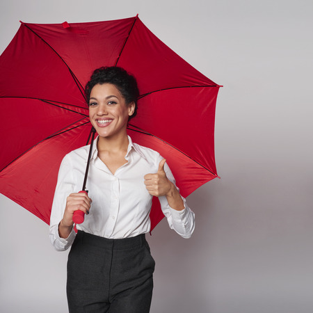 Happy african american business woman standing with red umbrella gesturing thumb up, over gray background