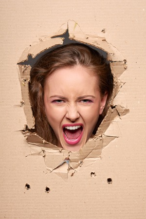furtively: Emotional screaming girl peeping through hole in paper Stock Photo