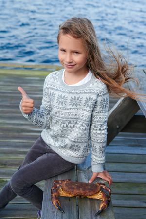 cangrejo: Niña que se sienta en la mesa por el mar, con la viva cangrejo noruego marrón, Cancer pagurus, buey de mar, Tourteau cangrejo en el banco, haciendo un gesto pulgar hacia arriba, al aire libre
