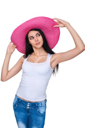 envisioning: Playful casual girl in bright pink summer straw hat looking away out of frame holding brims, over white background Stock Photo