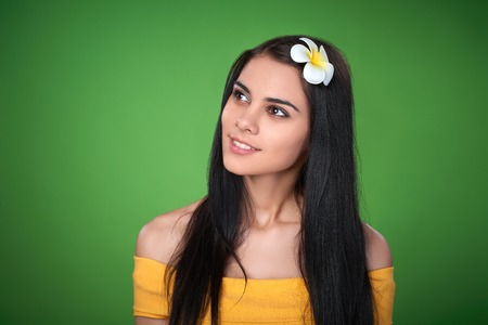 envisioning: Closeup portrait of beautiful smiling female in yellow dress and Plumeria Flower in hair looking at blank copy space over green background