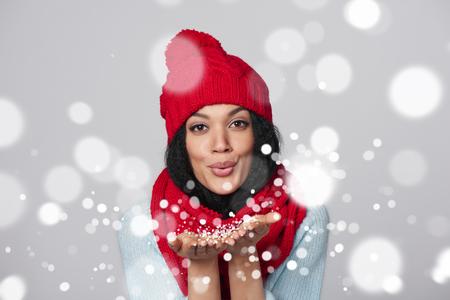 Fille de Noël. Métisse afro-américaine - caucasien femme portant un foulard tricoté chapeau chaud et de la poudrerie à vous, regardant la caméra, sur fond gris