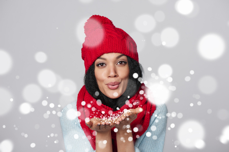 Christmas Girl. Mixed race african american - caucasian woman wearing knitted warm scarf and hat blowing snow at you, looking at camera, over gray background