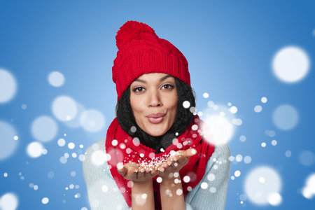Caucasian woman: Christmas Girl. Mixed race african american - caucasian woman wearing knitted warm scarf and hat blowing snow at you, looking at camera, over blue background Stock Photo