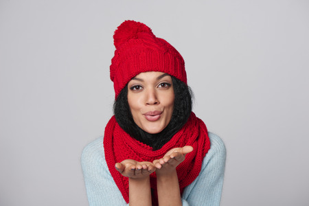 Christmas Girl. Mixed race african american - caucasian woman wearing knitted warm scarf and hat blowing a kiss, looking at camera, over gray background Stock Photo