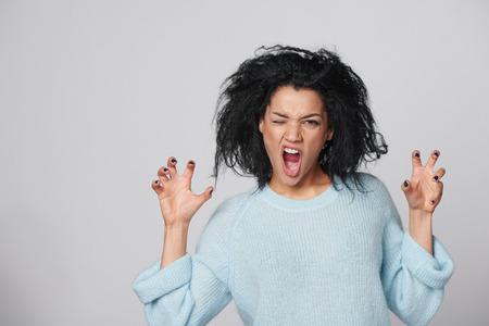 Toont haar wilde kant. Jong gemengd ras Afro-Amerikaanse - blanke vrouw poserend in wollen trui grommen naar je en gebaren een klauw vorm met haar handen, over grijze achtergrond