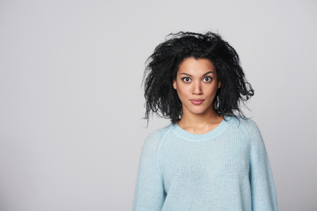 widely: Young mixed race african american - caucasian girl knitted sweater with crazy expression on her face with widely opened eyes, over gray background Stock Photo