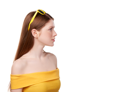 redheaded: Closeup profile of calm redheaded female wearing bright yellow strapless top and yellow sunglasses looking forward, over white background