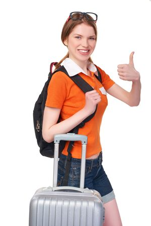 mochila viaje: Portrait of smiling redhead girl with backpack and suitcase gesturing thumb up, over white background Foto de archivo
