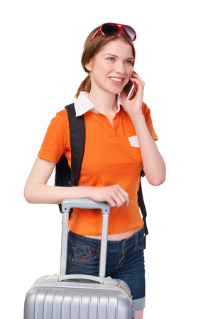 over white: Smiling redhead girl with backpack and suitcase talking on cell phone, over white background Stock Photo