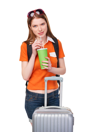 white paper: Smiling redhead girl with backpack and suitcase holding a drink in disposable paper cup, over white background Stock Photo