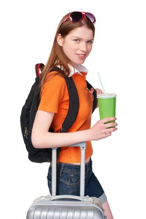 camera girl: Smiling redhead girl with backpack and suitcase holding a drink in disposable paper cup, over white background Stock Photo