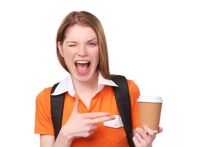 woman pointing: Closeup of excited young teen girl pointing at disposable paper cup with copy space, over white background