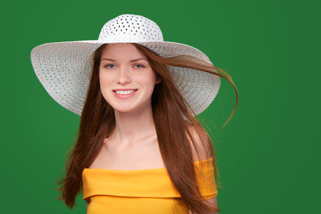 strapless: Closeup portrait of smiling pretty girl in yellow strapless summer dress and wide-brimmed straw hat with flying hair, over green background